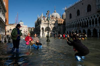 Tourists take photos in the flood St. Mark\'s Square in Venice on Nov. 14, 2019.