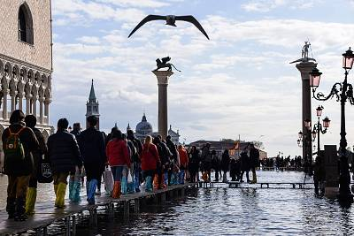People walk on a footbridge across the flooded St. Mark\'s Square by the statue of the Lion of St. Mark and the Column of St. Theodore of Amasea on Nov. 14, 2019 in Venice.