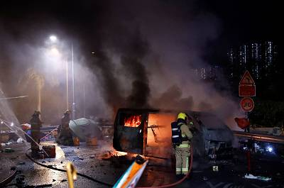 Firefighters extinguish a fire from explosions in an abandoned car, set up by protesters, near a barricade above the Tolo Highway next to the Chinese University campus in Hong Kong, China Nov. 15, 2019.
