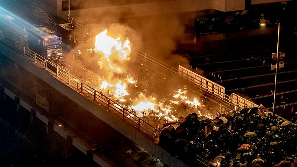 Image: A police vehicle burns as protesters and police clash on a bridge at