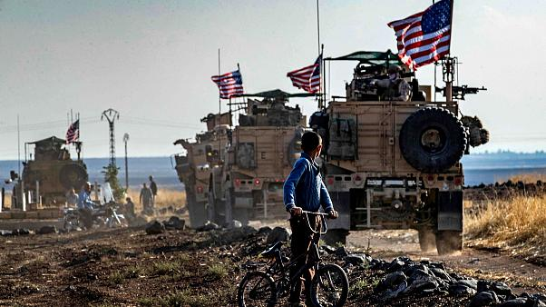 Image: A Syrian boy looks at a U.S. convoy patrolling near the Turkish bord