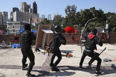 Protestors prepare to shoot bows and arrows during a confrontation with police at Hong Kong Polytechnic University in Hong Kong on Sunday.