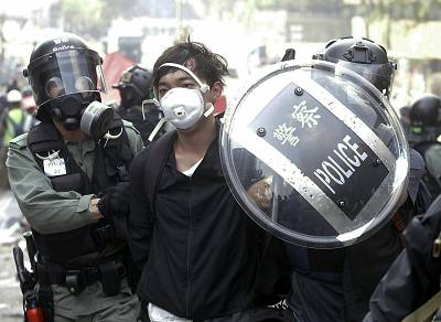 Police officers detain a protester near the Hong Kong Polytechnic University in Hong Kong on Monday.