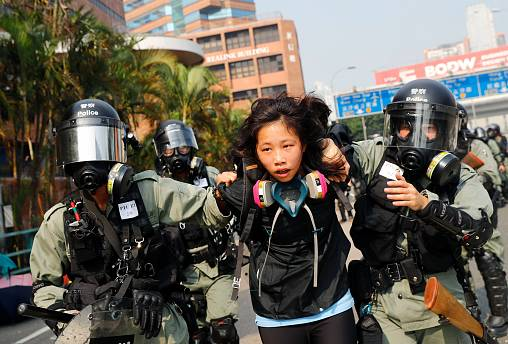 Image: A protester is detained by riot police while attempting to leave the