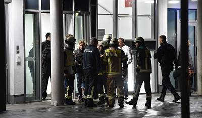 Policemen, firefighters and medical staff stand in front of the hospital after a doctor was stabbed to death as he delivered a lecture at the Schlosspark hospital in the western Berlin neighborhood of Charlottenburg, on Nov. 19, 2019.