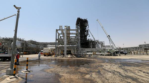 Image: Workers are seen at the damaged site of Saudi Aramco oil facility in