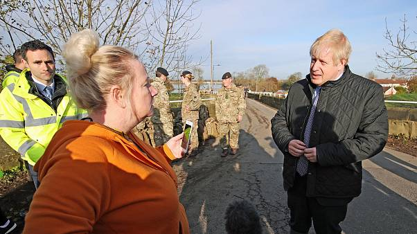 Image: Prime Minister Boris Johnson speaks with a local woman during a visi