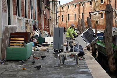 People remove damaged goods from a street in Venice after flooding.