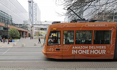 A South Lake Union streetcar with an advertisement for Amazon.com\'s same-day delivery service passes by an Amazon office building on Nov. 13, 2018, in Seattle.