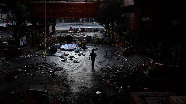 Image: A man walks past debris littering the entrance at the Hong Kong Poly