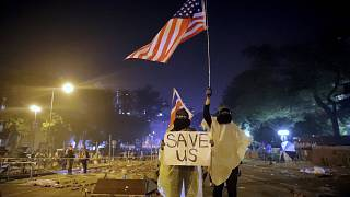 "Image: Protesters hold British and American flags and a sign reading ""Save"