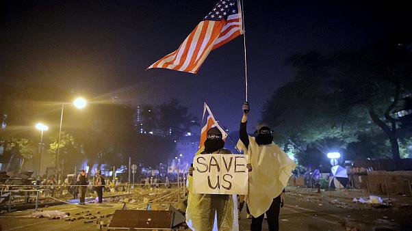 """Image: Protesters hold British and American flags and a sign reading """"Save"""