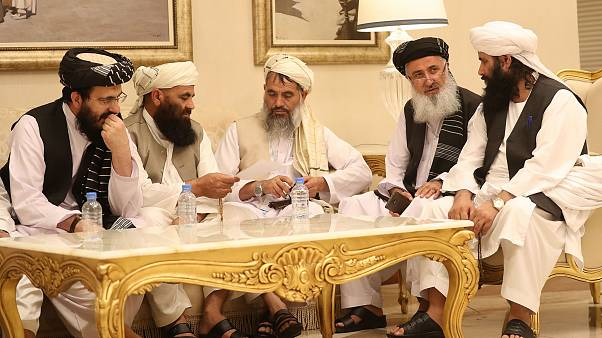 Image: Senior Afghans gather during talks with the Taliban in the Qatari ca