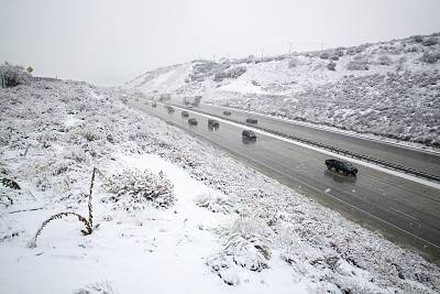 Snow falls along the Interstate 5 freeway at the Tejon Pass as travelers try to get in and out of Southern California for the Thanksgiving holiday on Nov. 27, 2019, near Gorman, Calif.