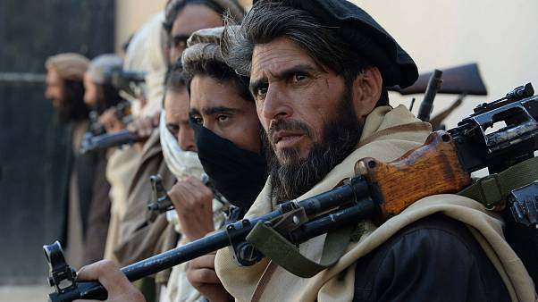 Image: Afghan alleged former Taliban fighters carry their weapons before ha