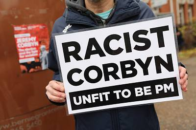 An activist holds a placard denouncing Labour leader Jeremy Corbyn outside the launch of the party\'s Race and Faith Manifesto on Nov. 26.