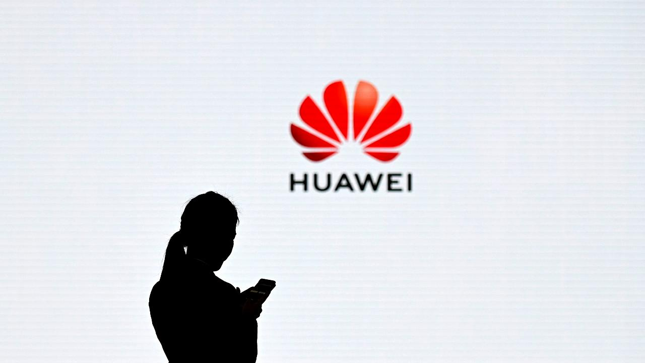 Image: An employee uses her phone at the Huawei Digital Transformation Show