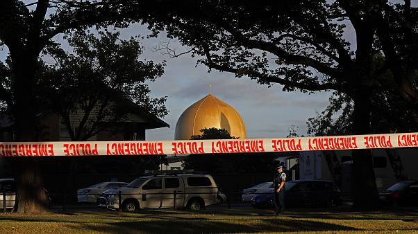 Image: A police officer stands guard in front of the Masjid Al Noor mosque