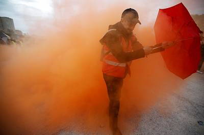 A protester holding an umbrella walks amongst smoke as French Labor unions members demonstrate against French government\'s pensions reform plans in Marseille on Friday.