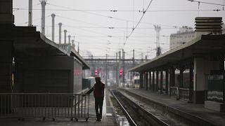 Image: A man stands on a deserted platform at the Gare de Lyon train statio