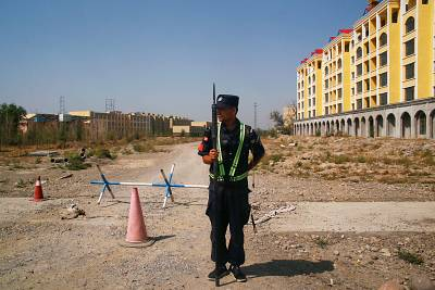 A police officer stands by the road near what is officially called a vocational education center in Yining in Xinjiang, China, on Sept. 4, 2018.