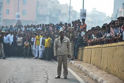 A Police personnel stands guard along a road as onlookers gather following a factory fire in Anaj Mandi area of New Delhi on December 8, 2019.