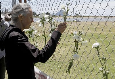 A woman places flowers at a fence on the waterfront in Whakatane New Zealand on Tuesday. Police said eight missing people are presumed dead and that some of the known injured could also die