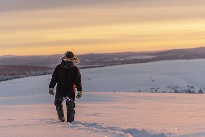 Reindeer herder Niila Inga from the Laevas Sami community walks across the snow as the sun sets on Longastunturi mountain near Kiruna, Sweden.