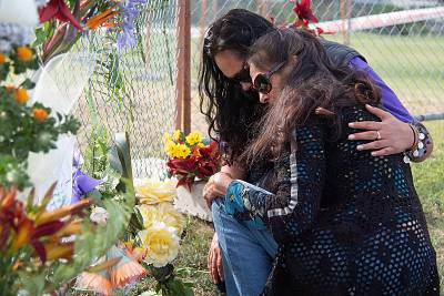 Mourners place flowers on the waterfront near the base of White Island Tours in the Bay of Plenty on Tuesday.