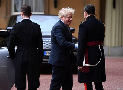 Prime Minister Boris Johnson is greeted by the Queen\'s Equerry-in-Waiting as he arrives at Buckingham Palace for an audience with Queen Elizabeth II on Friday.