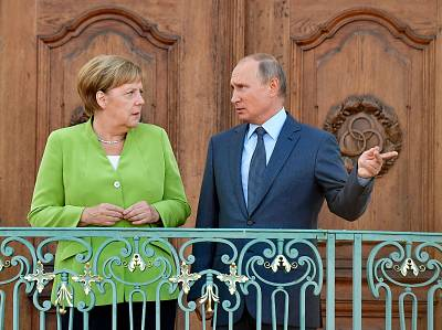 German Chancellor Angela Merkel and Russian President Vladimir Putin chat as they pose for the media at Schloss Meseberg castle in Meseberg, northeastern Germany where they met to discuss conflicts in Syria and Ukraine as well as energy issues.