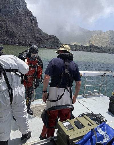 Police divers prepare to search the waters near White Island off the coast of Whakatane, New Zealand, Saturday Dec.14, 2019. A team of nine from the Police National Dive Squad resumed their search early Saturday for a body seen in the water following Monday\'s volcanic eruption.