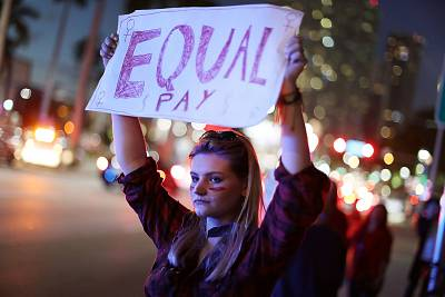 """A woman holds a sign that reads, """"Equal Pay"""" during """"A Day Without A Woman"""" demonstration on March 8, 2017 in Miami."""