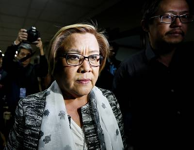 Senator Leila de Lima is escorted out of the Philippine Senate premises in Pasay city, south of Manila