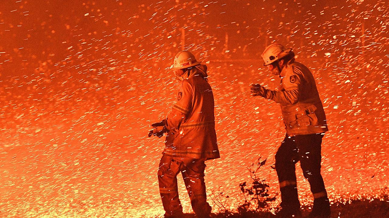 Firefighters struggle against the strong wind in an effort to secure nearby