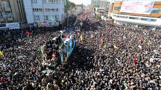 Image: Iranian mourners gather around a vehicle carrying the coffin of slai