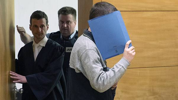 Image: A 57-year old defendant hides his face at the courtroom in Bielefeld