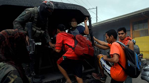 Image: Residents living near the erupting Taal Volcano are evacuated in Ago