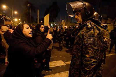 A woman attends talking to a policeman Saturday while attending a candlelight vigil in Tehran in memory of those killed in the plane crash.