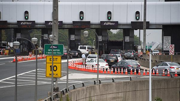 Image: A man gets out of his vehicle to see what the backup is at the toll