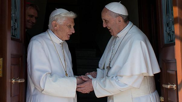 Image: Pope emeritus Benedict XVI, left, is welcomed by Pope Francis as he