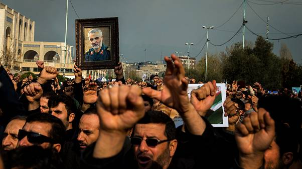Image: Protesters hold a photo of Iranian General Qassem Soleimani during a