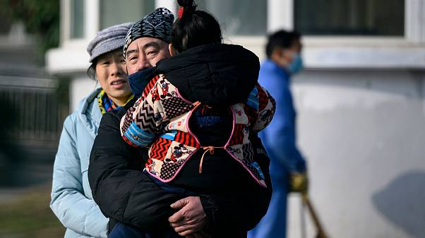 Image: A man holding her daughter leaves the Wuhan Medical Treatment Centre