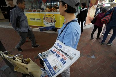 """A vendor gives out copies of newspaper with a headlines of """"Wuhan break out a new type of coronavirus, Hong Kong prevent SARS repeat"""" on a street in Hong Kong."""