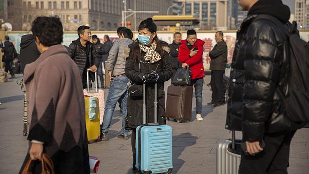 Image: A traveler wears a facemask as she stands near the Beijing Railway S