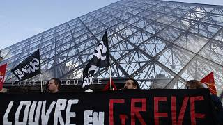 """Image: Striking employees hold a banner reading """"Louvre on strike"""" outside"""