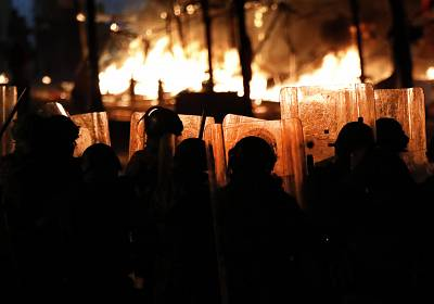 Riot policemen watch flames rise Saturday in Beirut from the tents of anti-government protesters, which where set on fire by civilian men believed to be the private unit of the parliament guards.