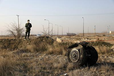 A police officer stands guard by debris from an Ukrainian plane that was accidentally shot down after taking off from Tehran on Jan. 8.