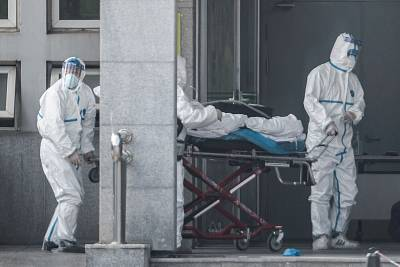 Medical staff carry a patient into the Jinyintan hospital, where patients infected by a mysterious SARS-like virus are being treated, in Wuhan, China on Saturday.
