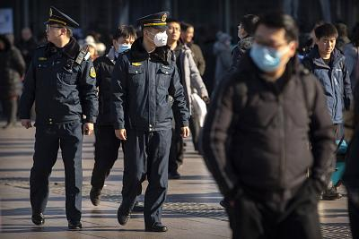 A security officer wears a face mask as he patrols outside Beijing Railway Station on Monday